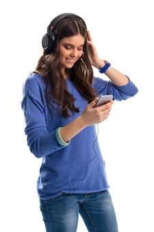 Женщина в наушниках улыбается. девушка в пуловере с телефоном. басы потрясающие. гаджеты высшего качества.