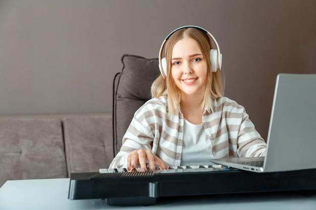 ヘッドフォンの女性は、家のインテリアでラップトップを使用してオンラインでピアノを弾くことを学びます。先生とのオンラインレッスン中に女性がシンセサイザーピアノを弾きます。ティーンエイジャーの女の子のレコードオンラインコンサートストリームのパフォーマー。