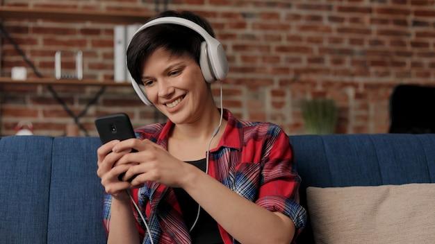 音楽アプリを使用してスマートフォンで音楽を聴いているヘッドフォンの女性。リラクゼーション、レジャー。