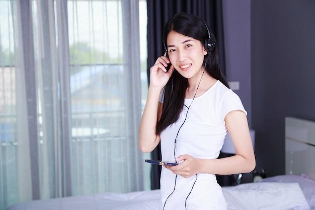 寝室のスマートフォンから音楽を聴くヘッドフォンの女性