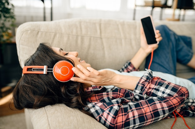 ソファで音楽を聴くヘッドフォンでの女性。