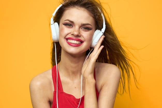 Женщина в наушниках слушает музыку в красной футболке, эмоции, мода, желтый образ жизни