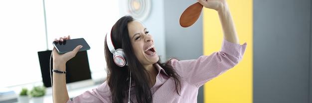 Женщина в наушниках на диване держит смартфон в руках и делает вид, что поет