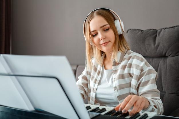 Женщина в наушниках играет фортепианную музыку на синтезаторе из нот. пианист-музыкант девушка-подросток совершенствует навыки игры на фортепиано. музыкальное образование по интересам - вокал - пение на музыкальном инструменте фортепиано.
