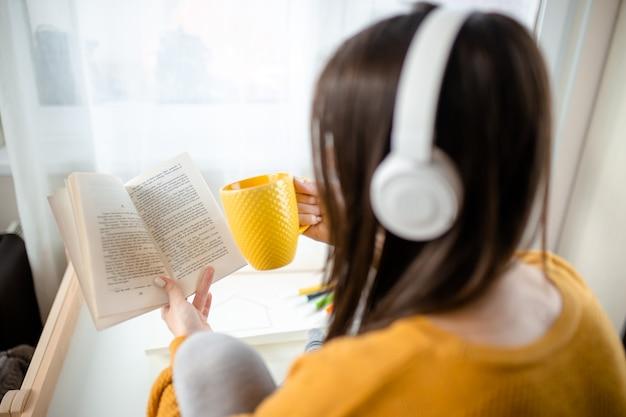 自宅で本を読んでヘッドフォンで女性、検疫レジャー。