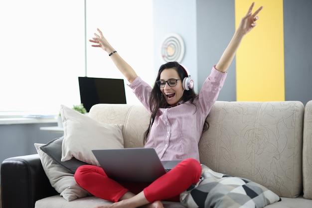 ヘッドフォンの女性は部屋のソファに座って喜ぶ