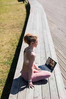 ノートパソコンでビデオを見ている木の遊歩道で屋外でヨガのポーズに座っているヘッドフォンの女性