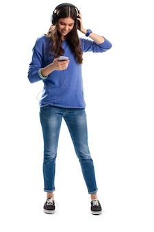 Женщина в наушниках улыбается. дама в толстовке держит телефон. новые наушники от известного бренда. лучшее качество звука.