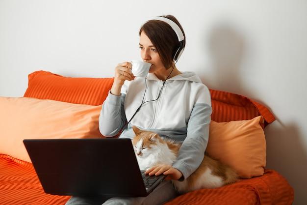 パソコンでヘッドフォンの女性はベッドの上に座って、コーヒーを飲みます。近くはキーボードで寝ている猫です