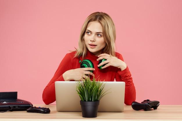 ノートパソコンの前にゲームパッドとヘッドフォンの女性は、テーブルエンターテインメントライフスタイルピンクの背景に座っています。高品質の写真