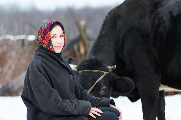 冬の庭の牛の近くのスカーフの女性