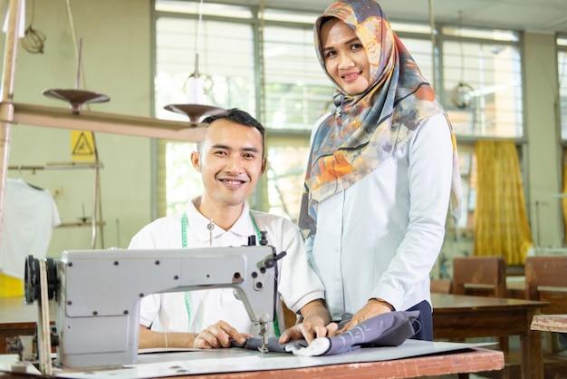 Женщина в платке, хозяйка конвекционной одежды, стоит рядом с работающим сотрудником