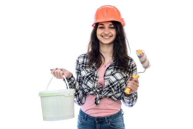 Женщина в шлеме с ведром с краской, изолированным на белой стене