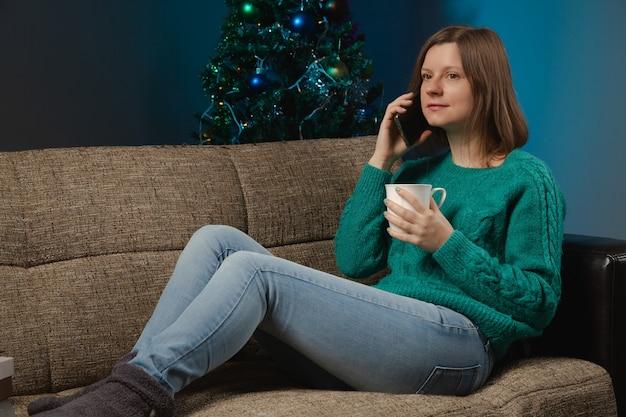 Женщина в своей квартире пьет горячий шоколад и разговаривает по телефону на рождество