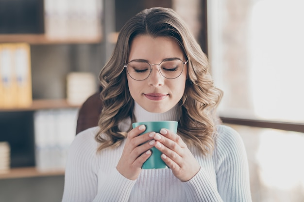 Женщина в офисе пьет кофе