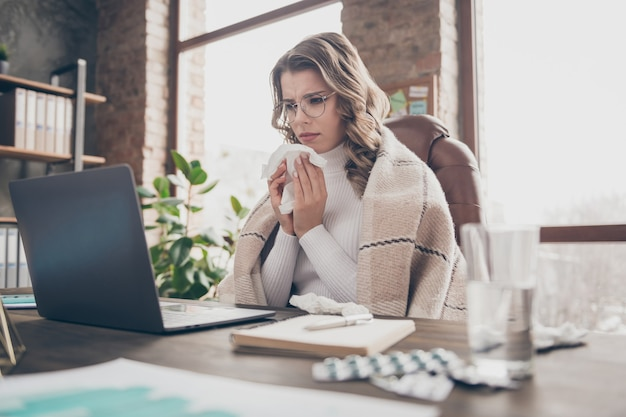 Женщина в своем офисе работает на ноутбуке во время болезни