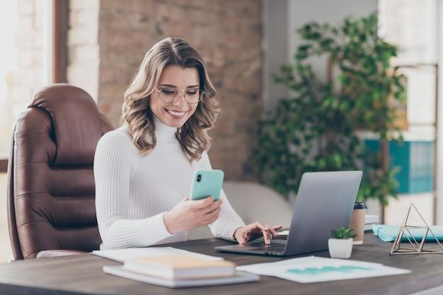 Женщина в своем офисе работает на ноутбуке