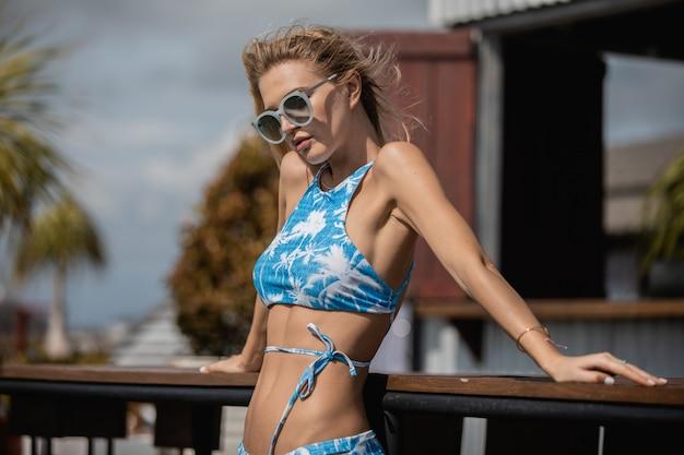 Женщина в купальниках и солнцезащитных очках в дневное время