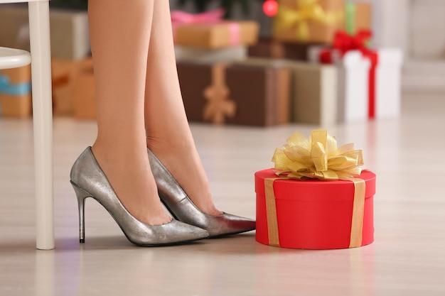 집에서 하이힐 신발과 선물 상자를 입은 여자