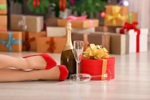집에서 하이힐 신발, 선물 상자, 샴페인 한 병을 신은 여성