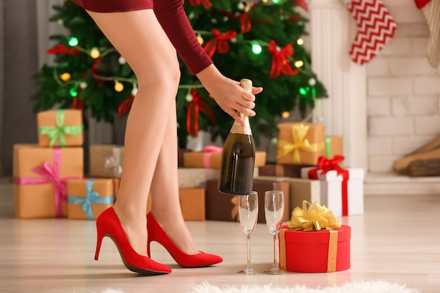 집에서 샴페인 한 병을 들고 하이힐 신발에 여자
