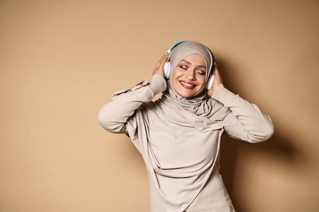 ヒジャーブとヘッドフォンの女性は、ベージュに対して音楽を聴きながら、かわいい笑顔とリラックス