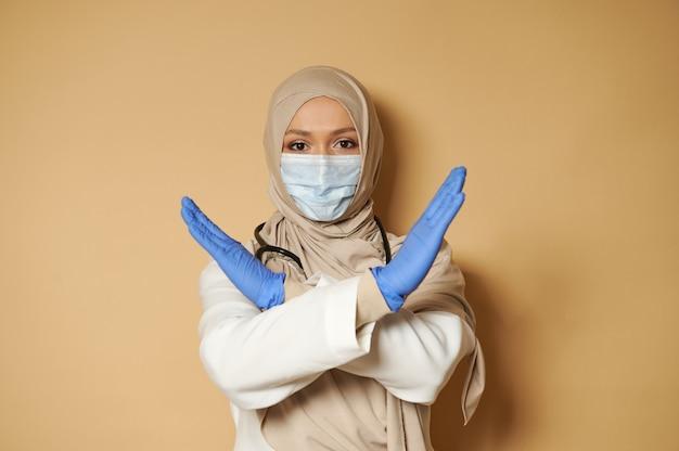コピースペースのあるベージュの表面に否定と拒否を表現するヒジャーブと医療マスクのジェスチャーの女性 Premium写真