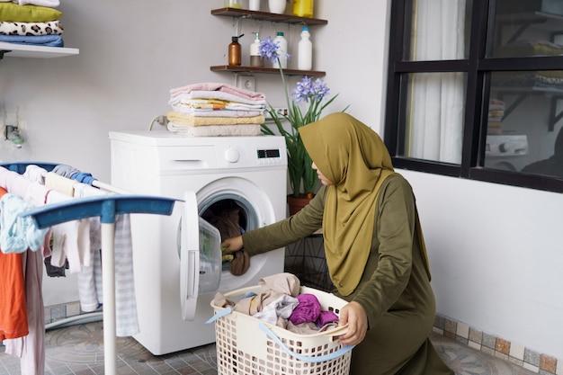 Женщина в хиджабе стирает одежду дома, используя стиральную машину