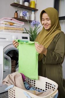 세탁기를 사용하여 집에서 의류 세탁을하는 히잡 여자