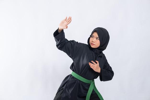 プンチャックシラットの制服を着たヒジャーブの女性がスタンスを提起し、攻撃をかわす