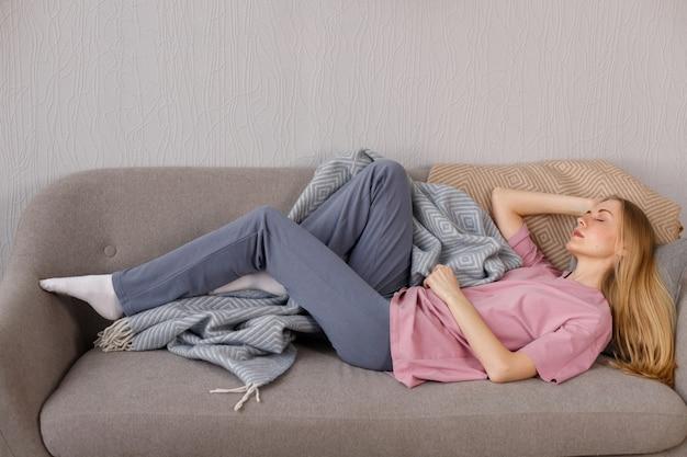 집에서 옷을 입고 여자는 소파에 누워