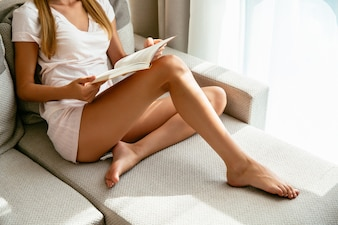 Woman in home clothing sitting on sofa and reading book at home