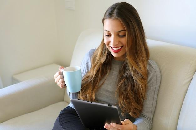タブレットを使用してソファに座って、コーヒーのカップを保持している家庭の居心地の良い服を着た女性