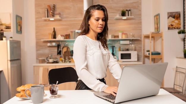 仕事の締め切りを終えるためにラップトップで作業している夜間の家庭の台所の女性。夕方の深夜にノートブックを使用して家庭の台所に集中した起業家。