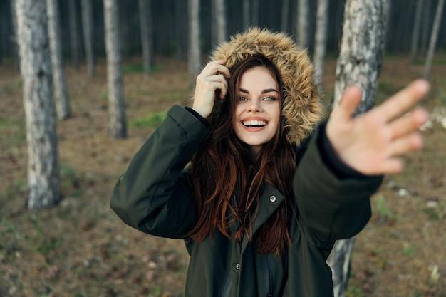 フード付きのジャケットを着た女性が腕を伸ばし、森の中を歩きます。高品質の写真