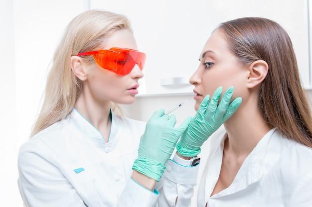 病院の服を着た女性は、手のひらに錠剤のセットを持っています。抗うつ薬を服用する不安定な精神の概念。ミクストメディア