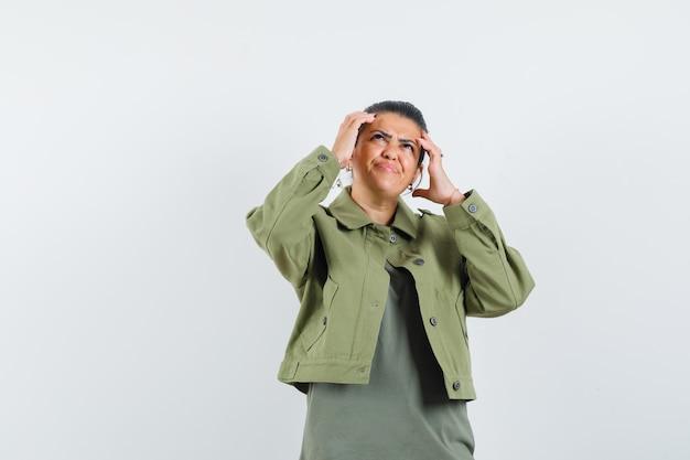 Женщина в куртке, футболке держится за голову и выглядит озадаченным