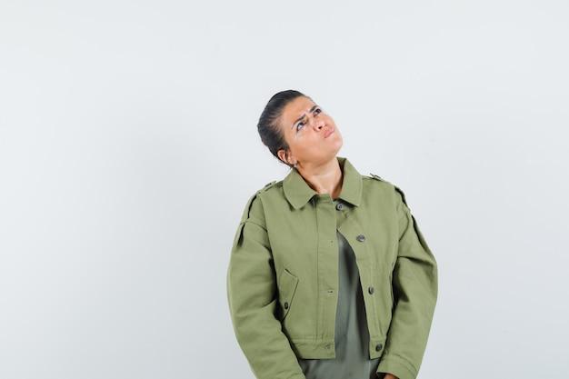 Женщина в куртке, футболке смотрит вверх и выглядит нерешительно