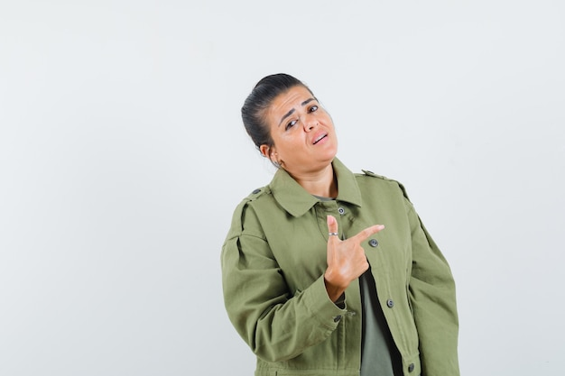 ジャケットを着た女性、右側を指して誇らしげに見えるtシャツ