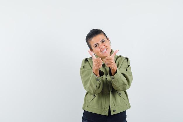 재킷에 여자, 두 엄지 손가락을 보여주는 티셔츠와 자신감을 찾고