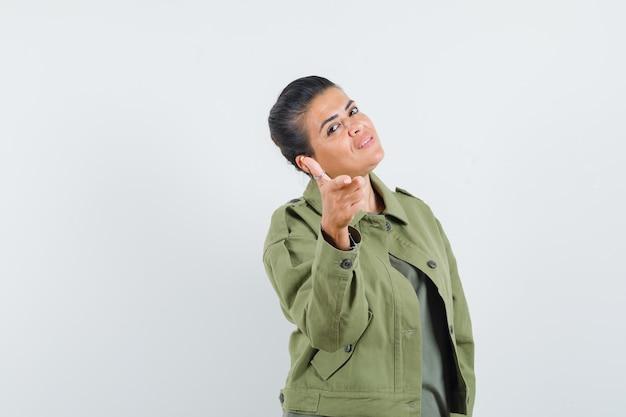 Женщина в куртке, футболке показывает жест пистолета и выглядит уверенно