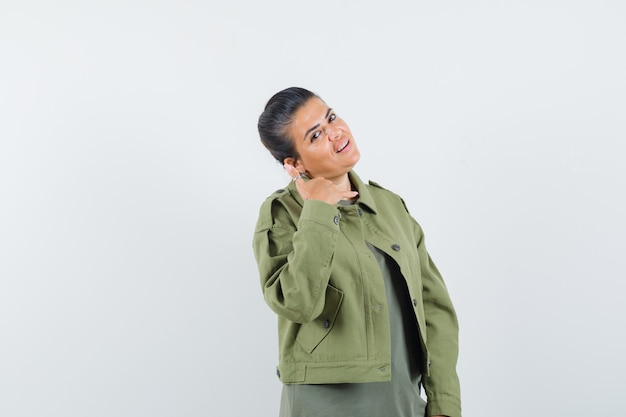 Женщина в куртке, футболке показывает жест телефона и выглядит уверенно