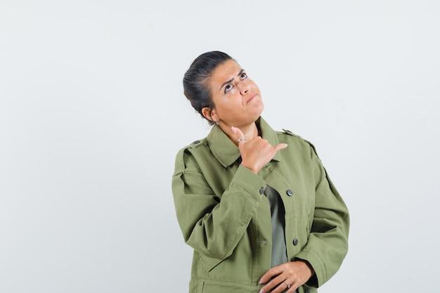 Женщина в куртке, футболке показывает жест телефона и задумчиво