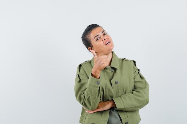 재킷에 여자, 엄지 손가락을 보여주는 티셔츠와 자랑스러워 보이는