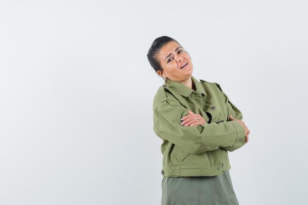 Женщина в куртке, футболке стоит со скрещенными руками и гордится