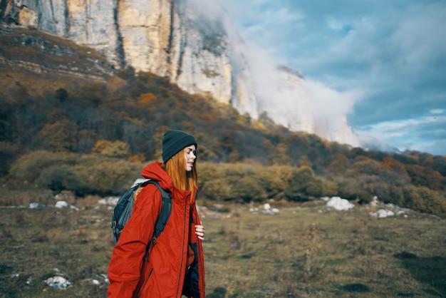 背中にバックパックを背負ったジャケットの帽子をかぶった女性は、山や自然の中で秋を歩きます