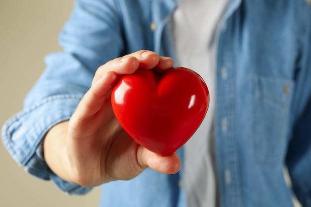 Женщина в джинсовой рубашке держит красное сердце