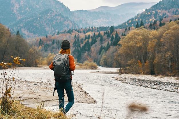山の風景の自然の川の近くでジーンズとバックパックを持ったジャケットを着た女性