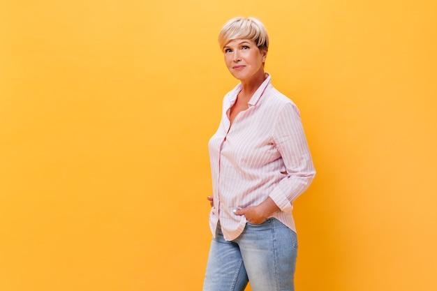 Женщина в джинсах и рубашке позирует на оранжевом фоне