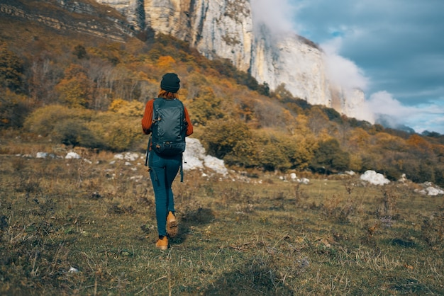 ジーンズ ブーツの女性とバックパック付きのセーターは、秋の山で休んでいます。